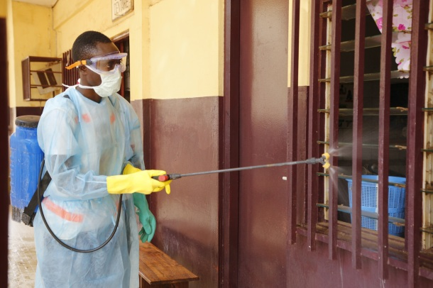 A volunteer with the Red Cross Soceity of Guinea disinfects a hospital in Coukray, Guinea. Photo: Idrissa Soumaré