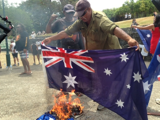 A man burns the Australian Flag at Emma Miller Place South Brisbane. Photo Kasun Ubayasiri