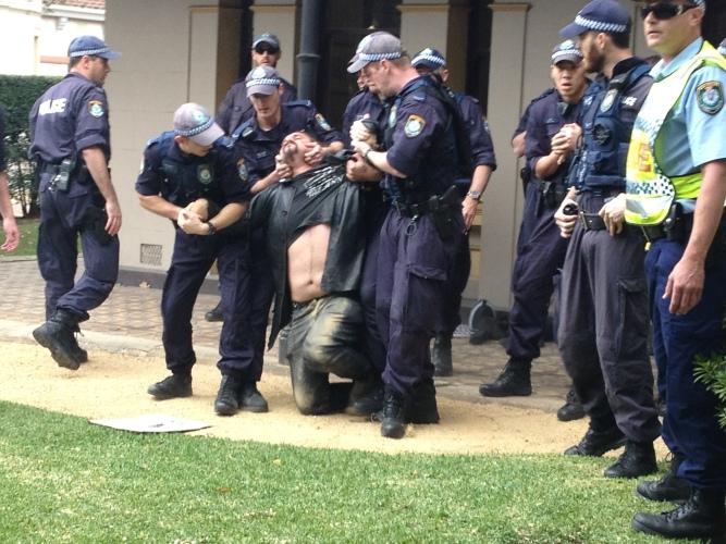 Ploice restraining man. Source: Wikipedia